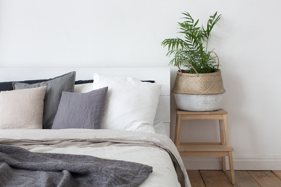 Bed with white and grey linens and a lot of pillows. Piece of interior of the bedroom with a bed, pillows of a headboard and a bedside tube in the form of a stool stairs with a basket and home plant