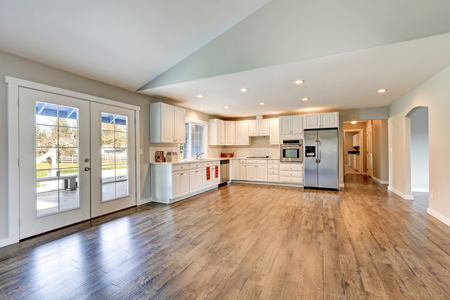 Spacious rambler home interior with vaulted ceiling over glossy laminate floor. Empty light filled dining or living space adjacent to new white kitchen room features pale grey walls