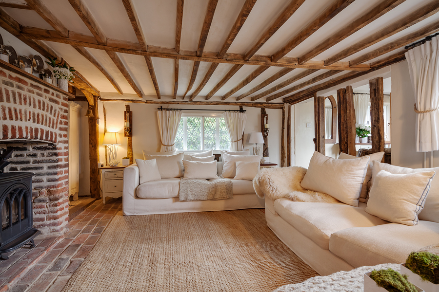 16th Century English cottage living room with cast iron fire beutifully decorated in pastel colours and wooden flooring