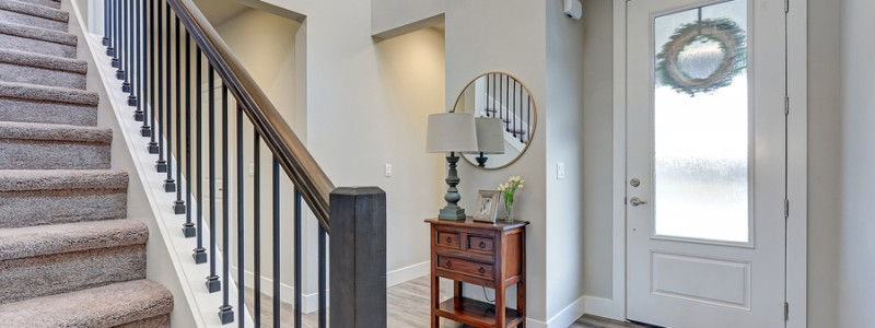 Grey foyer with laminate flooring high ceiling furnished with console table next to white front door and staircase with metal and wood railings.