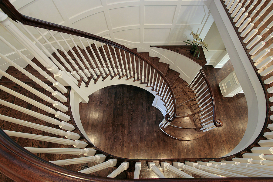 Spiral staircase in luxury home with wood railing and flooring