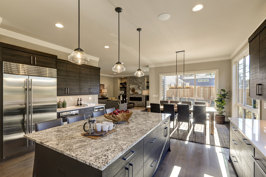 Modern gray kitchen features dark gray cabinetry paired with white quartz countertops and a glossy gray linear tile backsplash. Bar style kitchen island with granite counter.