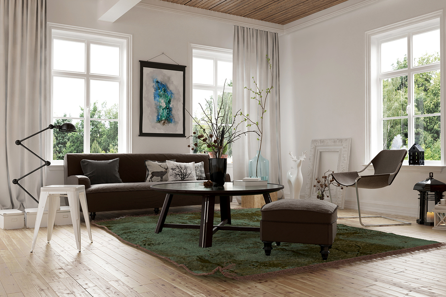 Cozy homely living room interior with a sofa, stools and chairs arranged in the corner surrounded by bright windows looking onto garden greenery.