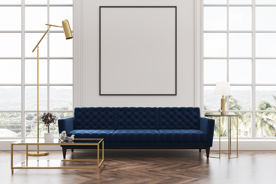White living room interior with a wooden floor loft windows a blue sofa a coffee table and a framed vertical poster on a white wall. 3d rendering mock up