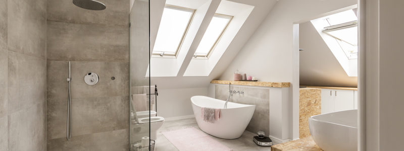 Modern bathroom interior with minimalistic shower and lighting white toilet sink bathtub and roofwindows