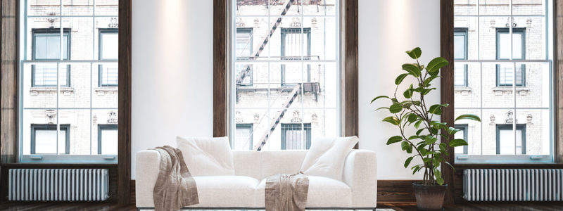 Elegant minimalist apartment living room interior with large windows and a single white couch with cushions and throw rugs on a small carpet over a wood floor.
